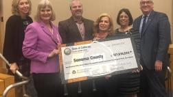 Assemblymember Aguiar-Curry presents check for $157,615,534 to Sonoma County Board of Supervisors - Lynda Hopkins, Susan Gorin, Chair James Gore, Shirlee Zane, David Rabbitt
