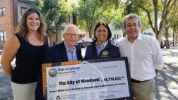 Assemblymember Aguiar-Curry presents check for $16,710,822 to City of Woodland Fiscal Officer Kim McKinney, Councilmember Tom Stallard, and City Manager Paul Navazio